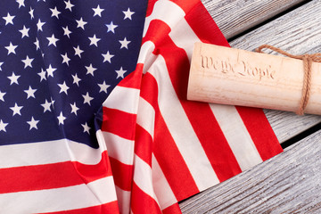 Constitution of the US and USA flag. American flag with rolled-up of constitution document on wooden table.
