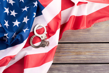 USA flag and handcuffs, top view. USA flag with steel handcuffs and copy space. USA legal system concept.