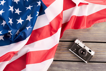 Vintage film camera and USA flag. Old retro camera and national flag of America on wooden background, top view. Memorial Day concept.