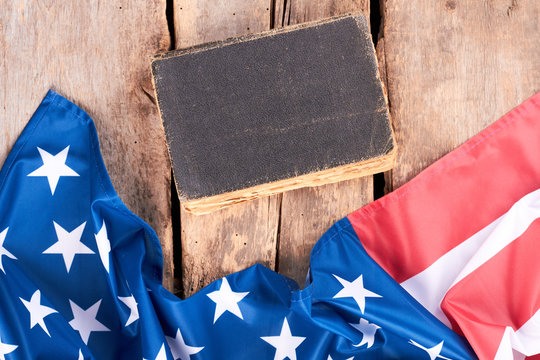 Closed vintage book and USA flag. United States satin flag and old hardcover book on rustic wooden boards.