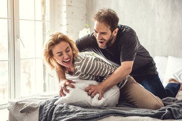 Jolly couple is playfully spending time in lit bedroom. Woman is laughing while her partner is leaning over her. They are having fun on cozy bed among pillows and blanket