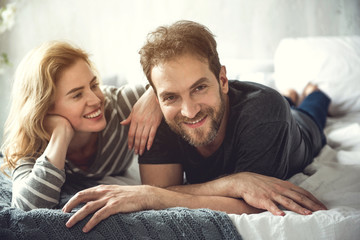 Cheerful bearded man is lying with soulmate on bed. He is looking at camera while woman is tenderly bonding him. Happy relationships concept