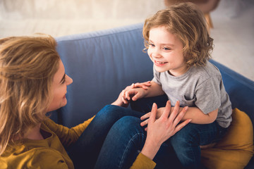 Mom and kid are grinning and looking into each-other eyes while staying down on sofa. They are joyfully hand-holding and boy is sitting on parent feet. Mother and child together concept