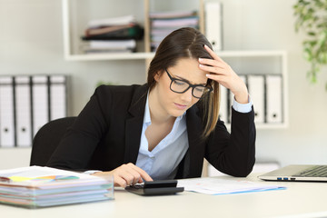 Worried bookkeeper calculating expenses at office