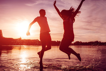 Happy couple jumping on summer river bank. Young man and woman having fun at sunset. Guys hanging together Wall mural