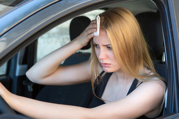 woman tired of heat in a car in summer