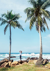 Southern point Sri Lanka island - Dondra cape, woman looks on palm trees crowns