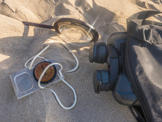travel searching concept, compass binoculars and magnifier on the sand