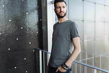 Photo of a beautiful stylish guy, hipster, dressed in a gray empty t-shirt, standing near the window, on a black wall background. Empty space for logo or design.