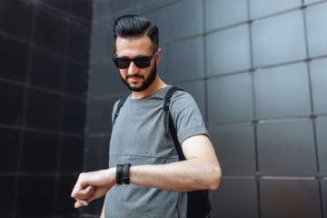 Portrait of a beautiful stylish guy, hipster with glasses, who looks at the clock, dressed in a gray empty t-shirt, standing on a black wall background. Empty space for logo or design.