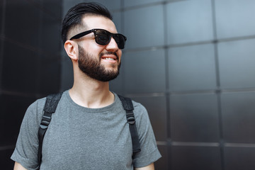 Portrait of a beautiful stylish guy, hipster with glasses, dressed in a gray empty t-shirt, standing on a black wall background. Empty space for logo or design.