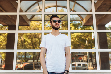 Portrait of a beautiful stylish guy, wearing glasses, on the background of a glass building, can be used for advertising, text insertion