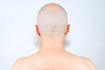 portrait of bald man with beard from back on light background
