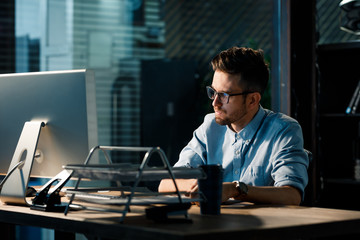 Young handsome man in glasses sitting alone in office and using computer doing overwork.