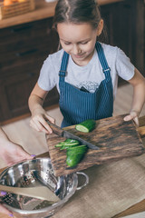 Little girl in apron putting cut cucumber pieces to the bowl on kitchen.