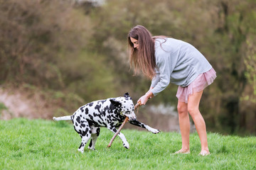 young woman plays with her Dalmatian dog