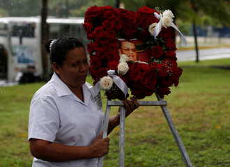 A woman holds a wreath with a picture of Cardinal Miguel Obando y Bravo during his funeral in Managua