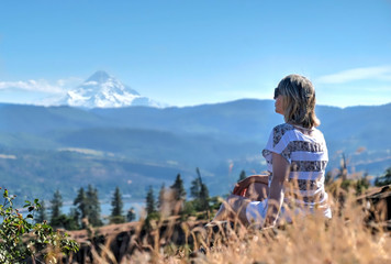 Woman in grass with view of Mount Hood. Columbia River Gorge. Catherine creek. Columbia River Gorge. The Dalles. Oregon. United States of Amrica. Wall mural