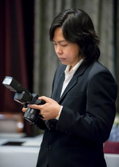 Asian long hair photographer in navy suit concentrated with his camera.