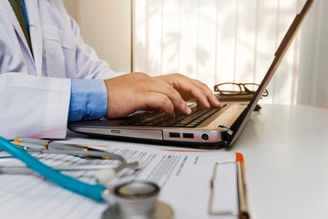 doctor sitting at the table near the window in hospital and typing at laptop computer