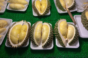 Pieces of durian fruit in white foam plate on display for sale.