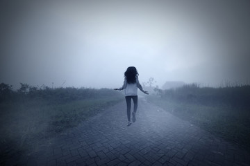 Spooky woman levitating in a misty morning