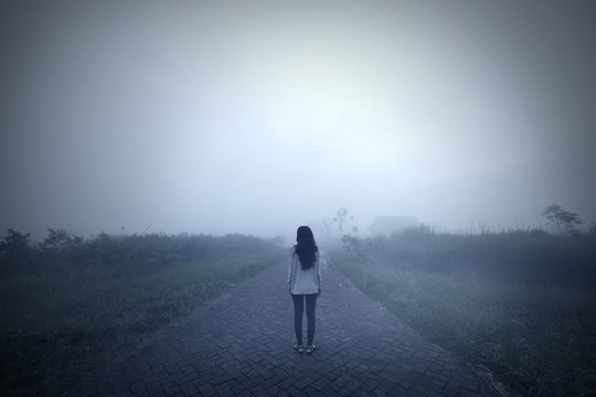 Sad woman standing alone in a misty morning