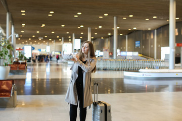 Female tourist wearing grey coat walking in airport hall with valise and looking at watch. Concept of traveling abroad and happy passenger.