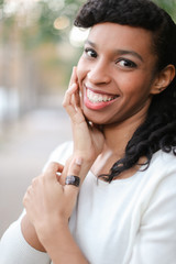 Portrait of young afro american female person with ponytail and ring smiling with white teeth. Concept of black beauty and positive emotions.