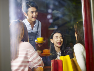 young smiling asian waiter serving coffee to customers