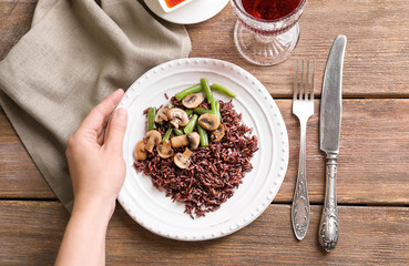 Woman holding plate with delicious brown rice, mushrooms and green beans