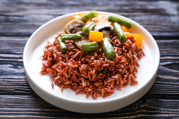 Plate with delicious brown rice and vegetables on wooden background