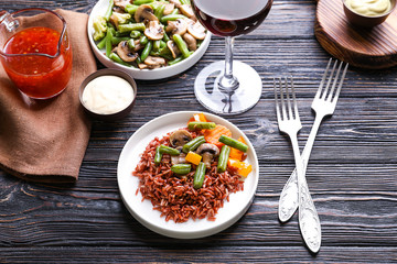 Plate with delicious brown rice and vegetables on dinner table