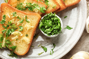 Plate with delicious homemade garlic bread, closeup