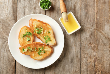 Plate with delicious homemade garlic bread on table