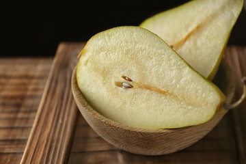 Bowl with delicious ripe pear on wooden surface