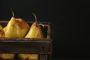 Wooden crate with delicious ripe pears on black background