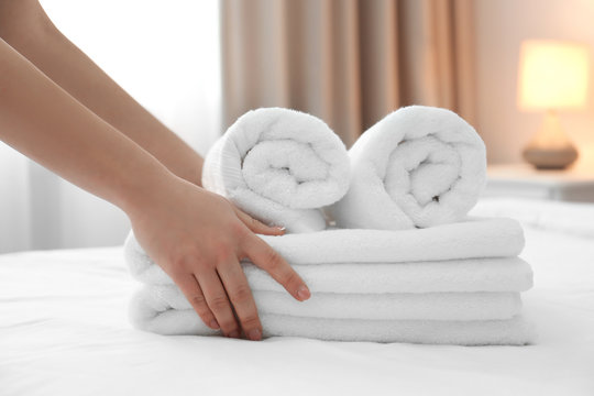 Chambermaid with stack of towels on bed in hotel room