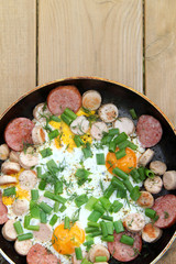 appetizer in a rustic/ fried eggs with sausages, sausage, onion and dill in a frying pan on the background of a wooden table