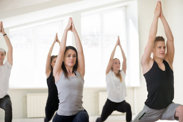 Group of young sporty people practicing yoga lesson, doing Warrior one exercise, Virabhadrasana 1 pose, working out, indoor session, students training in club, studio close up. Wellbeing lifestyle