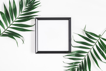 Tropical palm leaves, photo frame, on white background. Summer concept. Flat lay, top view, copy space