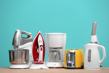 Household and kitchen appliances on table against color background. Interior element