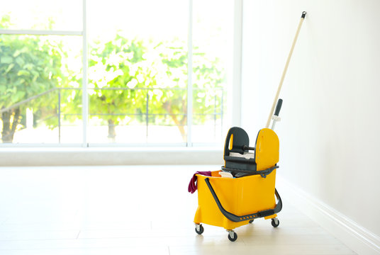 Mop bucket with cleaning supplies, indoors