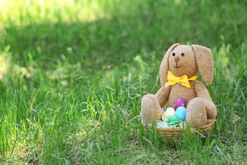 Toy bunny and basket with Easter eggs on grass