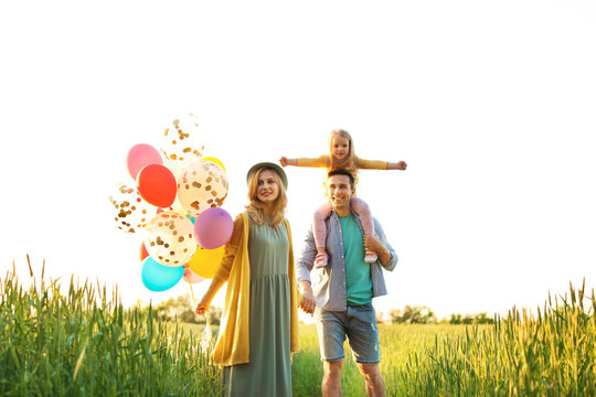Happy family with colorful balloons outdoors on sunny day