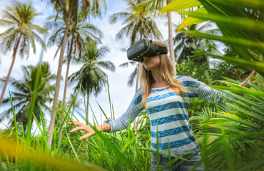 Virtual reality VR 3D headset and woman exploring the play on a background of nature jungle