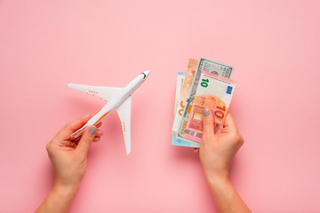 Plane and money in hand on a pink background.  Travel concept.
