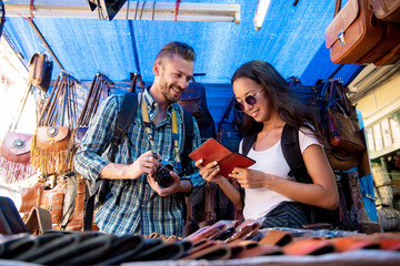 Couple tourists looking at leather products in shopping stall