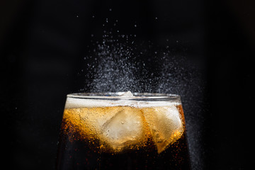 A glass of cola beverage with a salt close-up. On a black background.