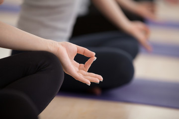 Sporty people practicing yoga lesson, sitting in Sukhasana exercise, Easy Seat pose, working out, indoor close up focus on mudra, studio. Mindful life, hobby, active lifestyle, wellness concept